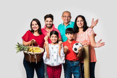 Famiglia indiana che si gode un picnic al chiuso - Multi generazione di famiglie asiatiche sedute su uno sfondo bianco con cesto di frutta, tappetino, calcio e bevande. messa a fuoco selettiva