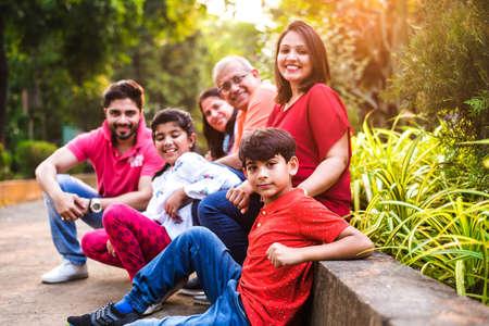 Indische Familie, die Picknick genießt - Mehrere Generationen asiatischer Familien, die über oder in der Nähe einer kleinen Mauer im Park sitzen, im Freien. selektiver Fokus Standard-Bild