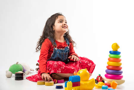 Cute Little Indian girl playing with colorful block toys over white background