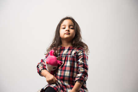 Indian small girl playing with soft toy, isolated over white background