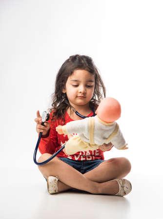 Indisches kleines Kindermädchen mit Stethoskop und ausgestopftem Baby- oder Welpenspielzeug, das vor weißem Hintergrund sitzt Standard-Bild