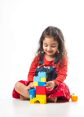 Cute Little Indian  girl playing with colourful block toys over white background Stock Photo