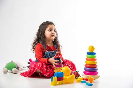 Cute Little Indian / Asian girl playing with colourful block toys over white background Stock Photo