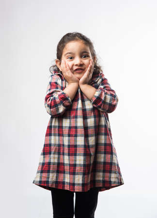 Happy  excited Indian Little kid girl with open mouth looking with surprised expressions. Standing isolated over white background 写真素材