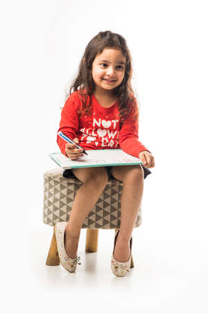small Indian girl writing on slate with marker pen, while sitting on stool over white background