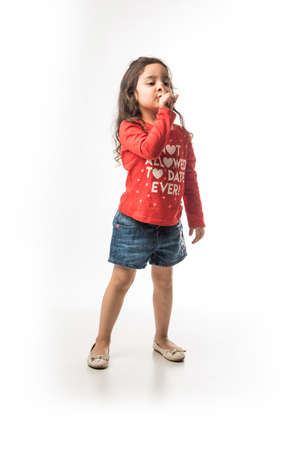 Indian small girl asks to keep silence / quiet with index finger on her mouth
