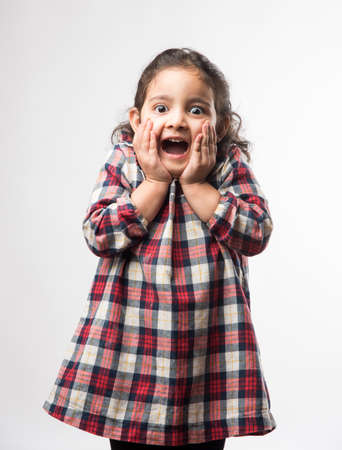 Happy / excited Indian Little kid girl with open mouth looking with surprised expressions. Standing isolated over white background 写真素材 - 132459732
