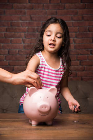 Indian small girl with piggy bank - saving concept
