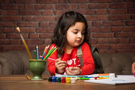 Indian small girl drawing  Painting with colours over paper, selective focus