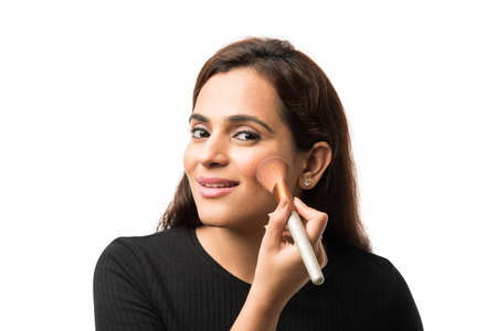 Indian young woman / Girl putting Makeup, standing isolated over white background Foto de archivo