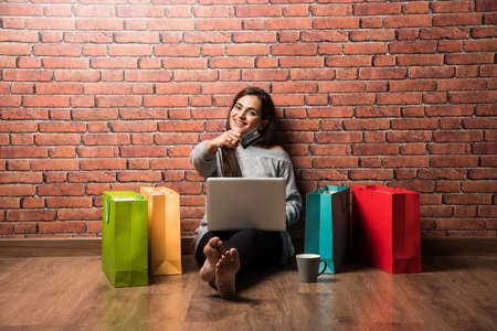 Indian girl shopping with debit  Credit card and laptop while sitting over wooden floor against red brick wall