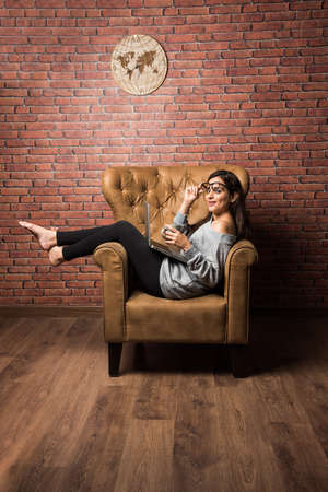 Indian girl with laptop sitting on wing chair against red brick wall 免版税图像 - 139728889