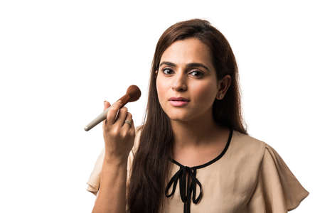 Indian young woman  Girl putting Makeup, standing isolated over white background Foto de archivo