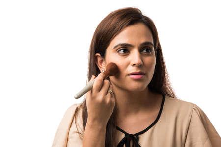Mujer joven india / niña poniendo maquillaje, que se encuentran aisladas sobre fondo blanco.