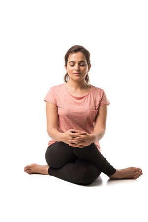 Indian Woman  Girl performing Yoga asana or meditation or dhyan, sitting isolated over white background Foto de archivo