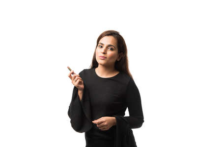 Indian young woman / Girl putting Makeup, standing isolated over white background
