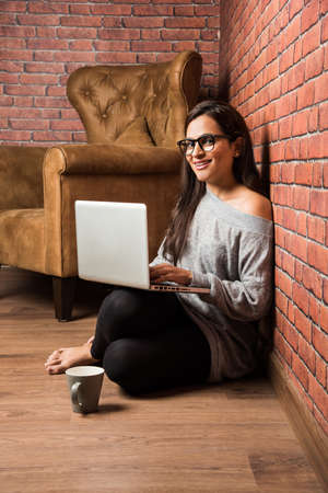 Indian girl with laptop sitting over wooden floor against red brick wall Foto de archivo