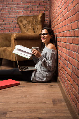 Indian  Asian woman studying with book and laptop on floor
