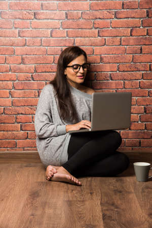 Indian girl with laptop sitting over wooden floor against red brick wall 免版税图像 - 139728444