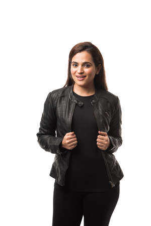 Portrait of Pretty Indian girl  woman or lady in black leather jacket, standing isolated against white background Foto de archivo