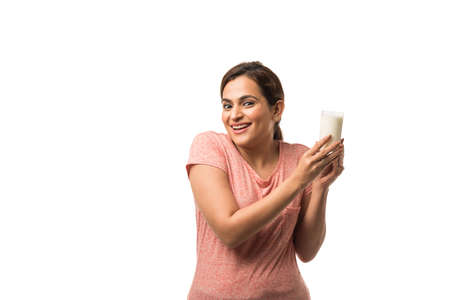 Portrait young Indianasian woman drinking milk from the glass isolated over white background