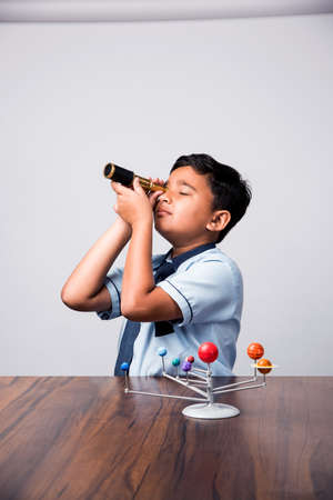 Indian School Kid studying Planets or planetary science with 3d Model of our solar system