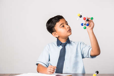 Indian school kid or science student Using Molecular Model Kit for studying physics, selective focus