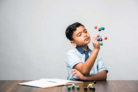 Indian school kid or science student Using Molecular Model Kit for studying physics, selective focus Imagens