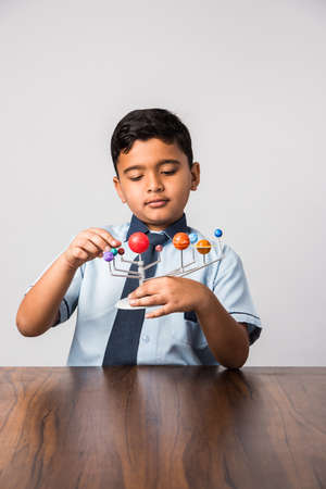Indian School Kid / Boy studying Planets or planetary science with 3d Model of our solar system