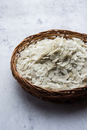 Raw Flattened Rice or Thick or thin Rice Flakes for Namkeen Chivda snacks or Aloo Poha for Indian Breakfast, served in a bowl