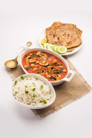 Mushroom sabzi in tomato curry with chickpea and spinach, Indian main course menu served with Paratha and cooked white rice