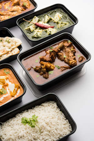 Online Food delivery concept Indian paneer butter masala and palak paneer, mutton & chicken curry with roti and rice in plastic containers, food like butter chicken, chicken