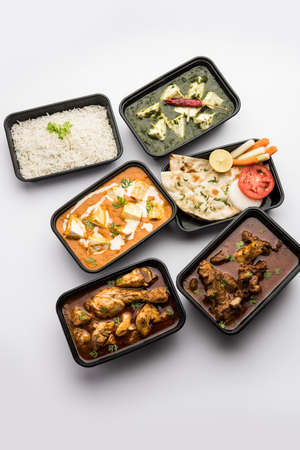 Online Food delivery concept Indian paneer butter masala and palak paneer, mutton & chicken curry with roti and rice in plastic containers, food like butter chicken, chicken Standard-Bild