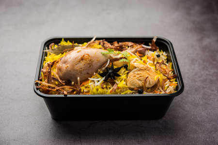 Restaurant style Chicken Tikka Biryani packed for home delivery in plastic box or container with Raita and salan