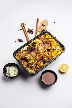 Restaurant style Gosht or Mutton Biryani or Pulao packed for home delivery in plastic box or container with Raita and salan