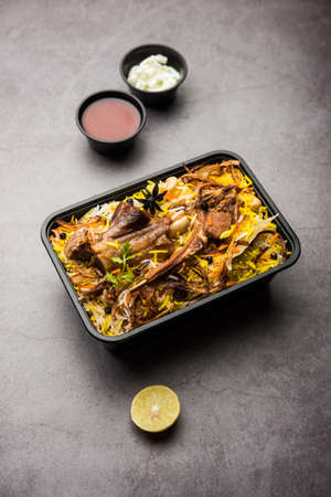 Restaurant style Gosht or Mutton Biryani or Pulao packed for home delivery in plastic box or container with Raita and salan Banco de Imagens