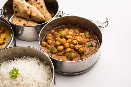 Indian vegetarian Lunch Box or Tiffin made up of stainless steel for office or workplace, includes Dal Fry, Chole Masala, Rice with chapati and salad Banco de Imagens