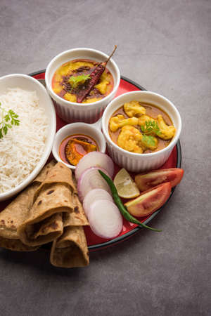 Indian Food Platter or Vegetarian Thali includes Dal Fry, Rice, Chapati and a type of vegetable with salad Stock Photo
