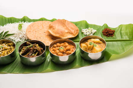 Traditional South Indian Meal or food served on big banana leaf, Food platter or complete thali.  selective focus