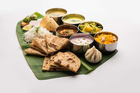 Maharashtrian food Thali or platter - Mumbai style Meal from Indian State Maharashtra includes, roti, rice, dal, sabji, sweet roti and rice, kadhi, Modak, papad etc