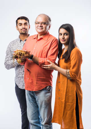 Indian old man with young son and daughter or couple holding gold jewelry, ornaments - Asset or Gold Loan concept
