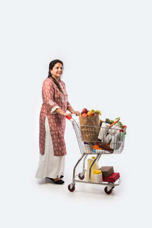Indian mid age woman with shopping cart or trolly full of grocery, vegetables and fruits. Isolated Full length photo over white background