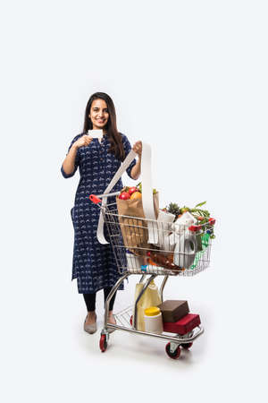 Indian young woman with shopping cart or trolly full of grocery, vegetables and fruits. Isolated Full length photo over white background