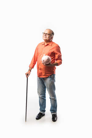 Indian senior adult or old man with piggy bank or money box Archivio Fotografico