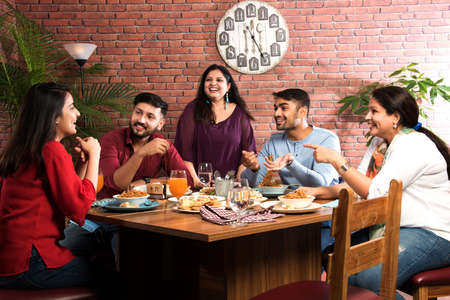 Indian friends eating or dining in restaurant. Asian people in face for get-together, reunion or celebrating party. Coffee Shop Celebration Friendship Togetherness concept Imagens