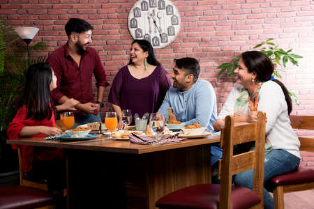 Indian friends eating or dining in restaurant. Asian people in face for get-together, reunion or celebrating party. Coffee Shop Celebration Friendship Togetherness concept