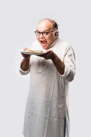 Indian asian senior or old man eating pizza while standing isolated against white background Stock Photo