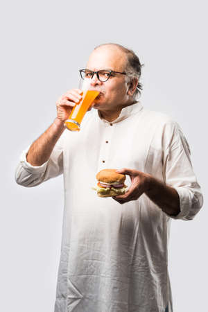 Indian Old Man eating burger or Hamburger with mango juice or cold drink
