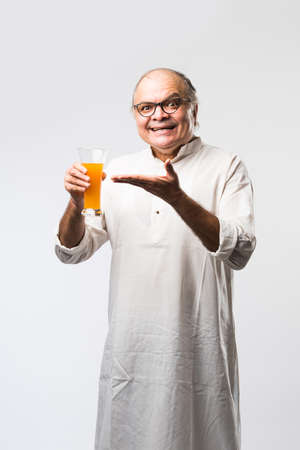 Happy senior Indian old man drinking or holding a glass of fresh orange or mango juice