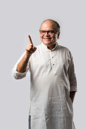 Portrait of cheerful Indian retired old man wears white kurta, pointing or presenting or in hands folded pose